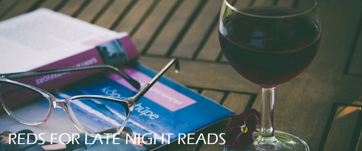 Reading glasses, book, glass of red wine.