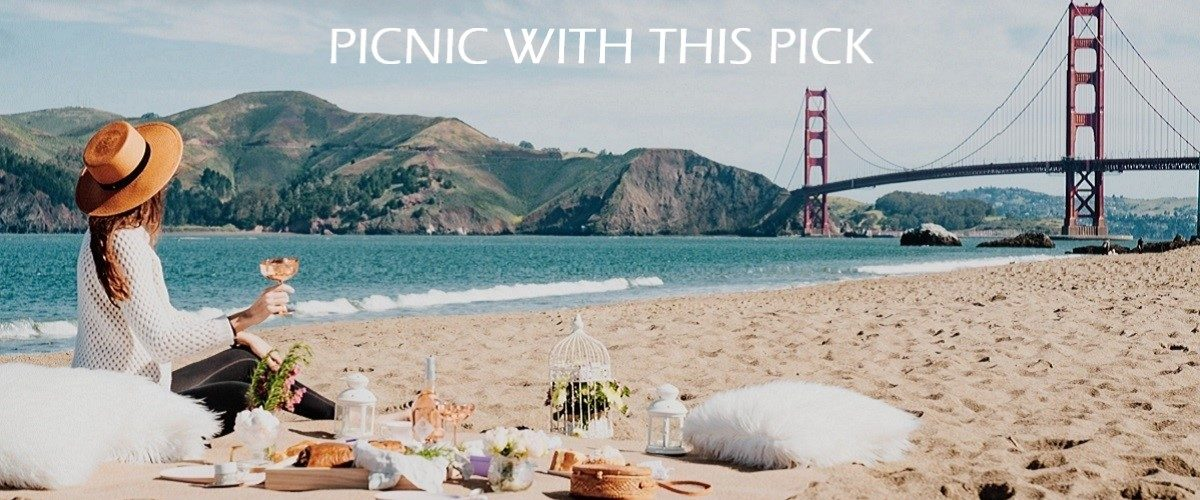 Woman picnics on the beach with wine.